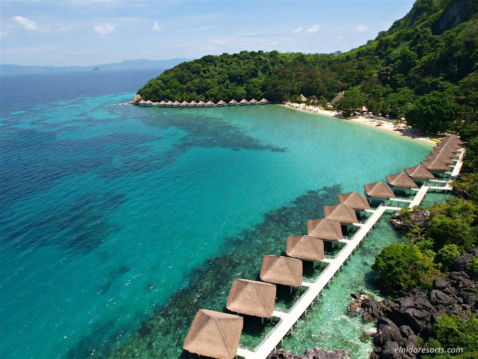 Thatched huts resting on the blue ocean in a cove filled with lush greenery at El Nido Resort Apulit Island, Palawan, Philippines