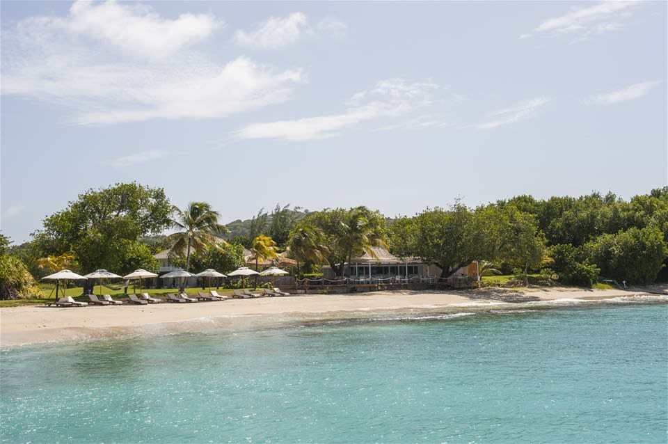 Rugged, white sand beach and swaying palm trees at Cotton House, Mustique, The Grenadines