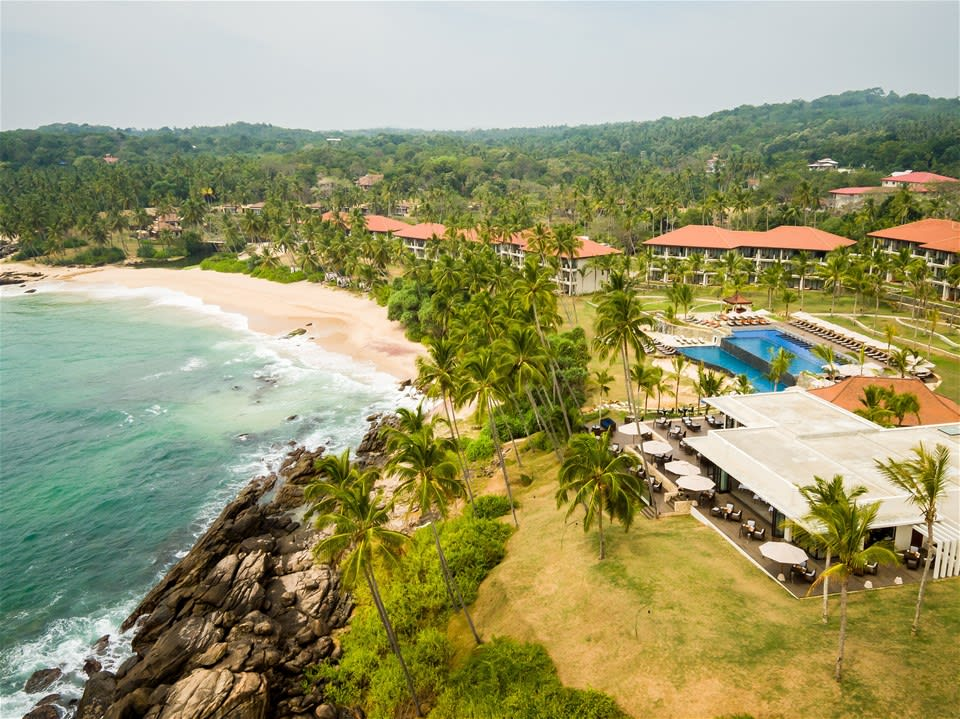 Ariel view of hotel, pool and restaurant, overlooking beach and ocean, at Anantara Peace Haven Tangalle Resort, Sri Lanka.