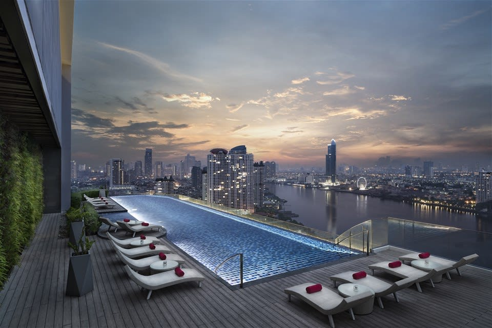 Loungers along the rooftop pool of Avani+ Riverside with a panoramic view over the Chao Praya river in Bangkok, Thailand