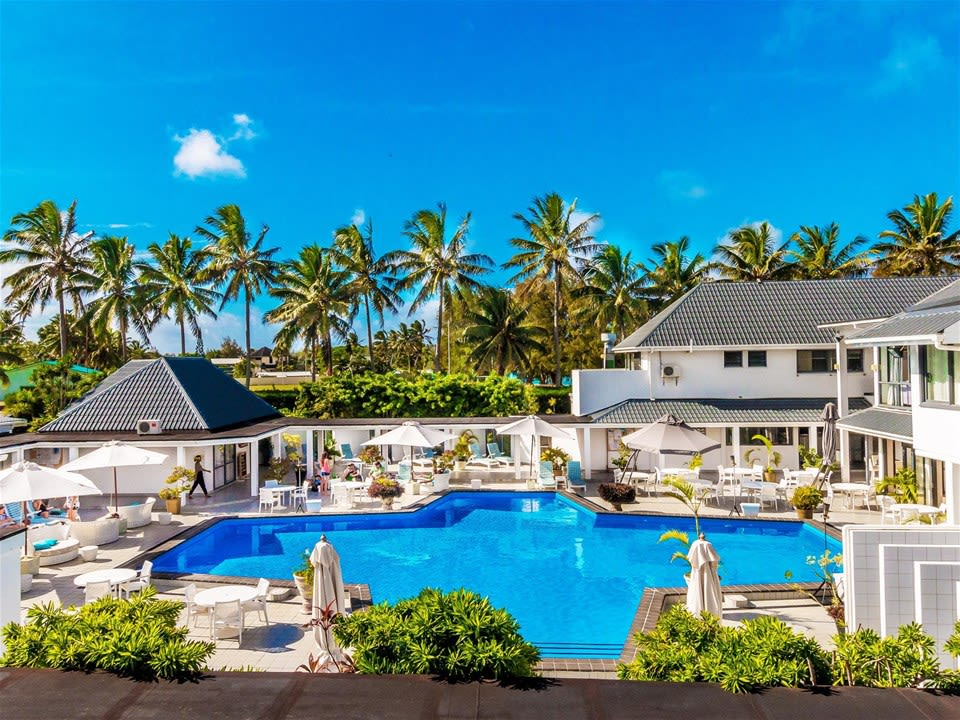 An intimate, boutique property surrounding an inviting swimming pool with a palm tree backdrop at Muri Beach Club