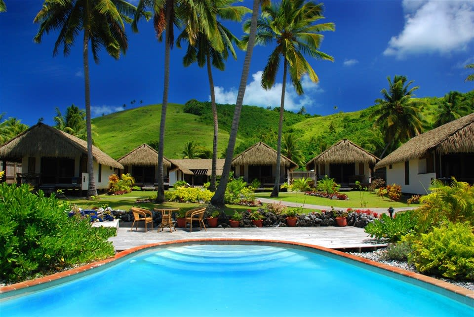 Thatched bungalows nestled in lush hilly terrain, conveniently located near the pool for a morning swim