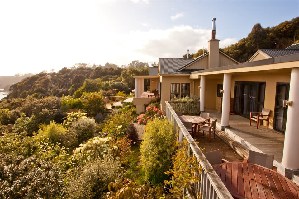 Stewart Island Lodge overlooks lush green hillside & out to Half Moon Bay from a spacious outdoor decking area