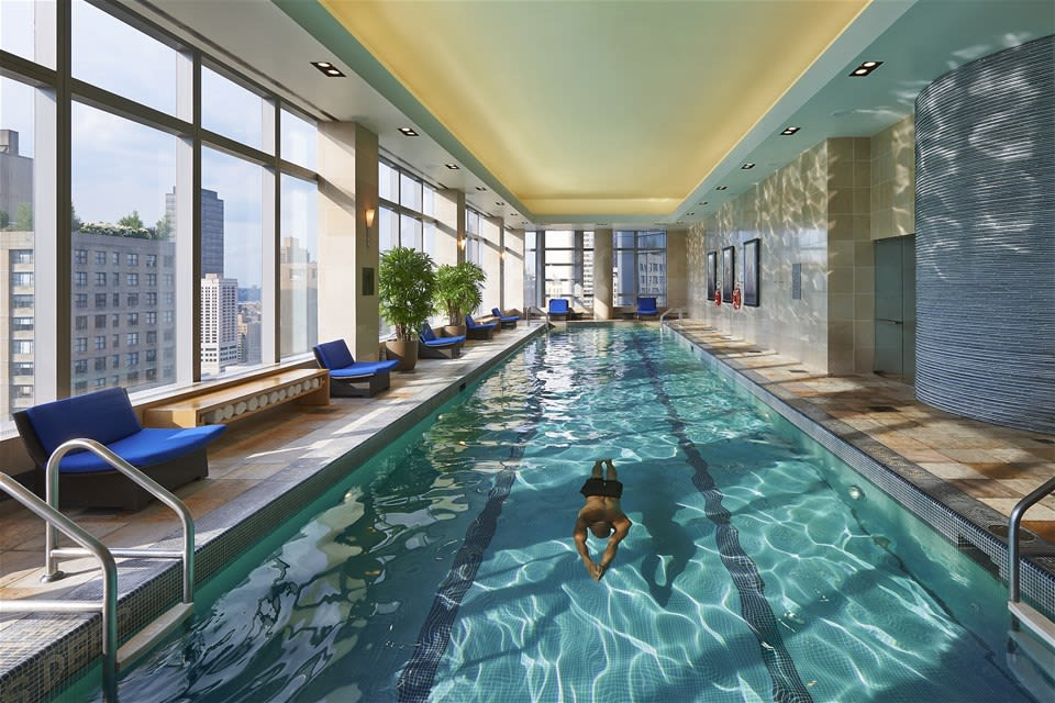Man swimming in the indoor pool of the Mandarin Oriental New York overlooking the Manhattan skyline USA