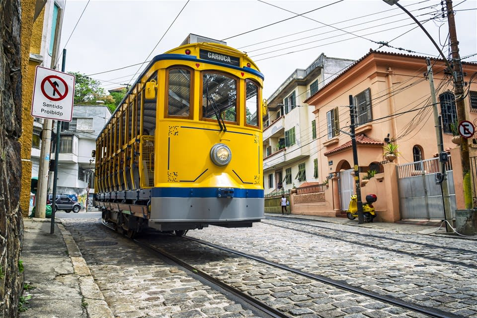 Yellow tram on a cobbled street, with traditional buildings in background, on Discover Santa Teresa, Rio De Janeiro, Brazil.