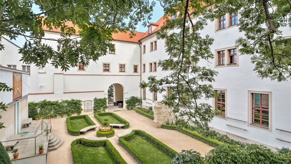 Landscaped courtyard garden at Augustine, Luxury Collection, Prague, enclosed by the cream and terracotta former monastery