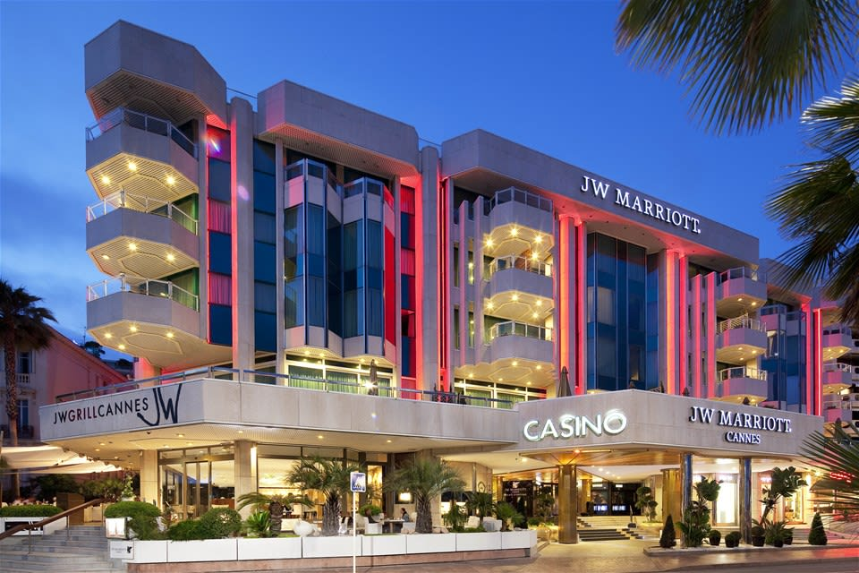 Stylish red night lighting frames the exterior of JW Marriott Cannes, France, showcasing the retro building design