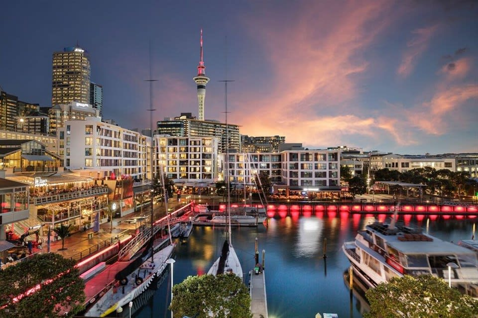 Light fades over Auckland Harbour as bars are bustling in the forefront of the Sky Tower at Sebel Auckland Viaduct Harbour