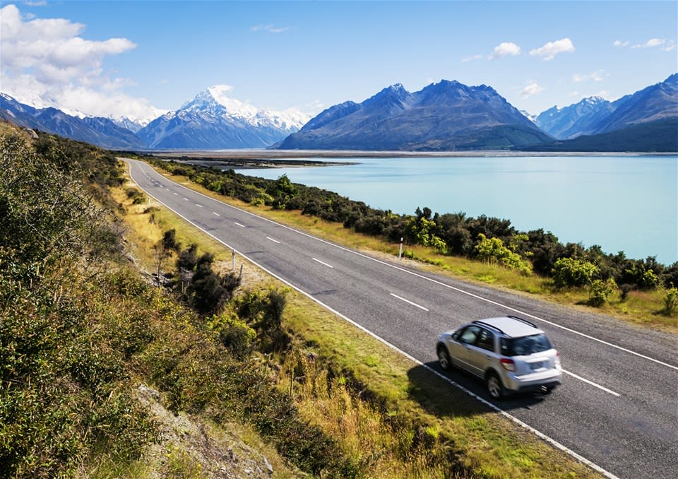 The open road in New Zealand with a car in the foreground and gorgeous mountain and lake views