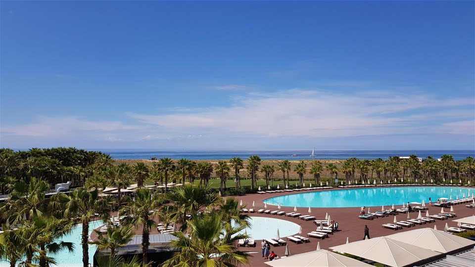Pools surrounded by loungers and palm trees at Vidamar Algarve Portugal overlooking the clear blue Ocean