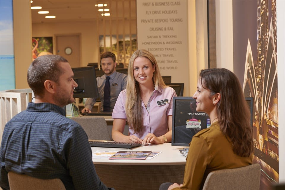 Experienced Trailfinders travel consultant with clients in the travel centre