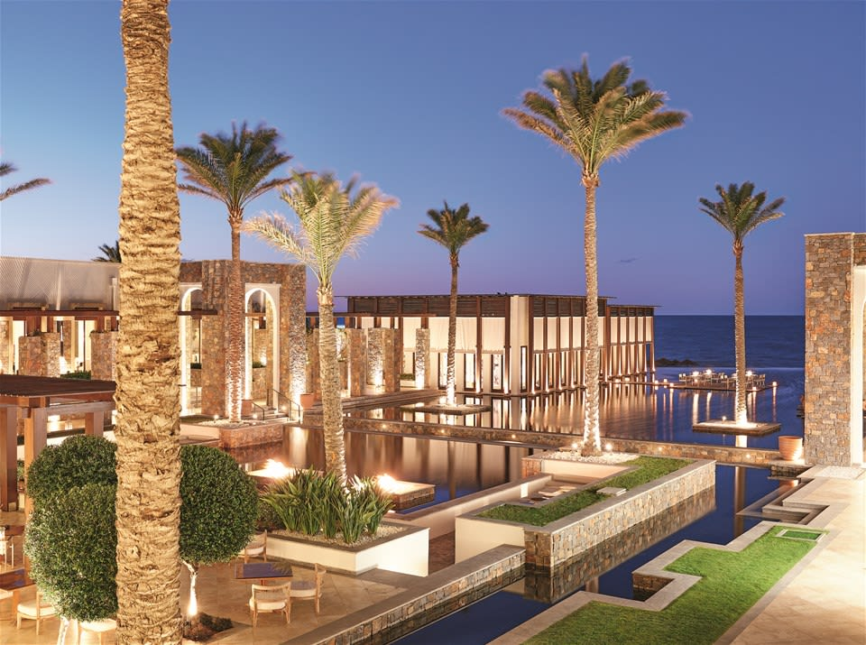 Serene evening landscape with palm trees and over-water restaurant looking out to the sea at Grecotel Amirandes, Crete