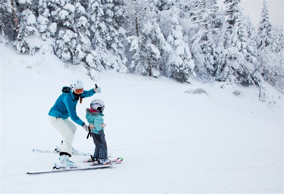 A mother teaching her child to ski down an easy slope in Mont Tremblant, Canada