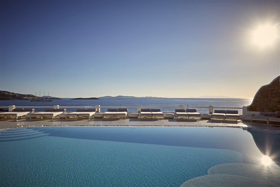 Sunlight reflects off the calm water of the pool at Kouros Hotel & Suites, Mykonos, Greece, with loungers overlooking the sea