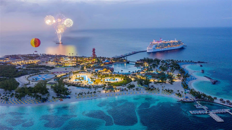Aerial view of the Harmony of the Seas cruise departing Royal Caribbean's private island at night with fireworks in the sky.