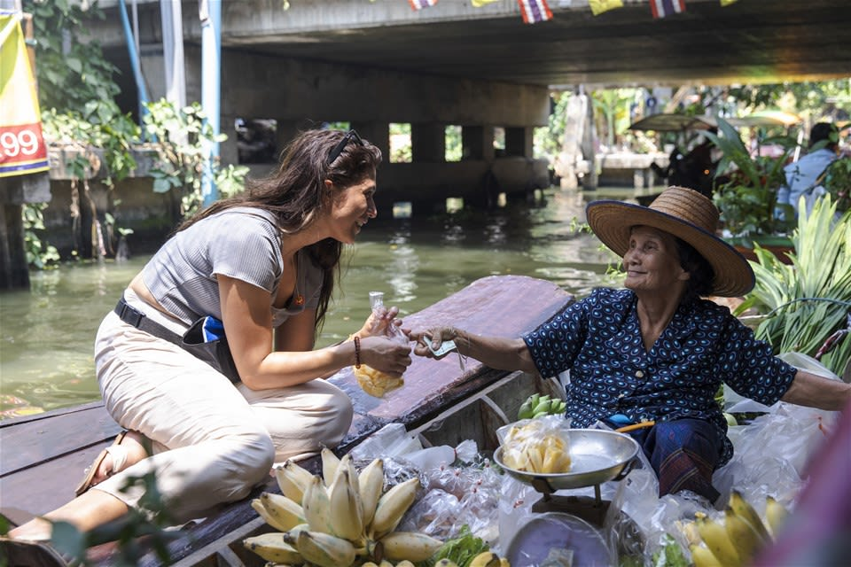 A smiling female buys a bag of mango from an elderly thai woman in a straw hat sitting on a boat, at Bangkok's floating market