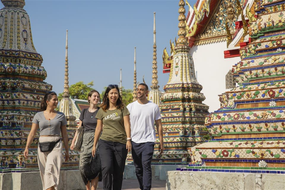 A female guide leads young travellers around the temples of Wat Pho, Bangkok
