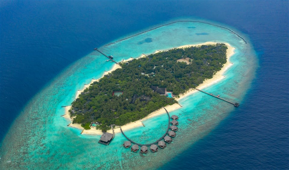 Resort from above with surrounding coral reef, overwater villa's and beachfront pool at the Adaaran Select Meedhupparu, Maldives
