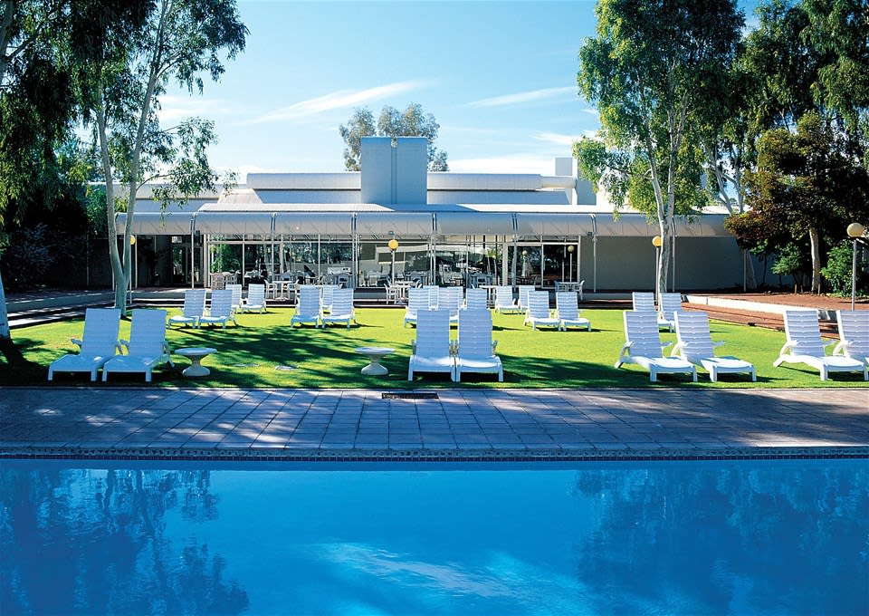 Clear blue pool surrounded by sun loungers at Voyages Desert Gardens Hotel, Ayers Rock Resort, Northern Territory, Australia
