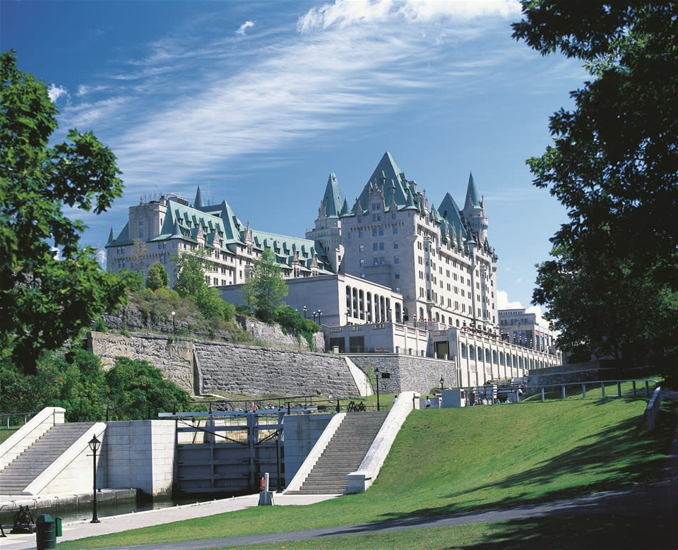 Exterior of large limestone Fairmont Chateau Laurier set on the banks of the Rideau Canal, Ontario Canada