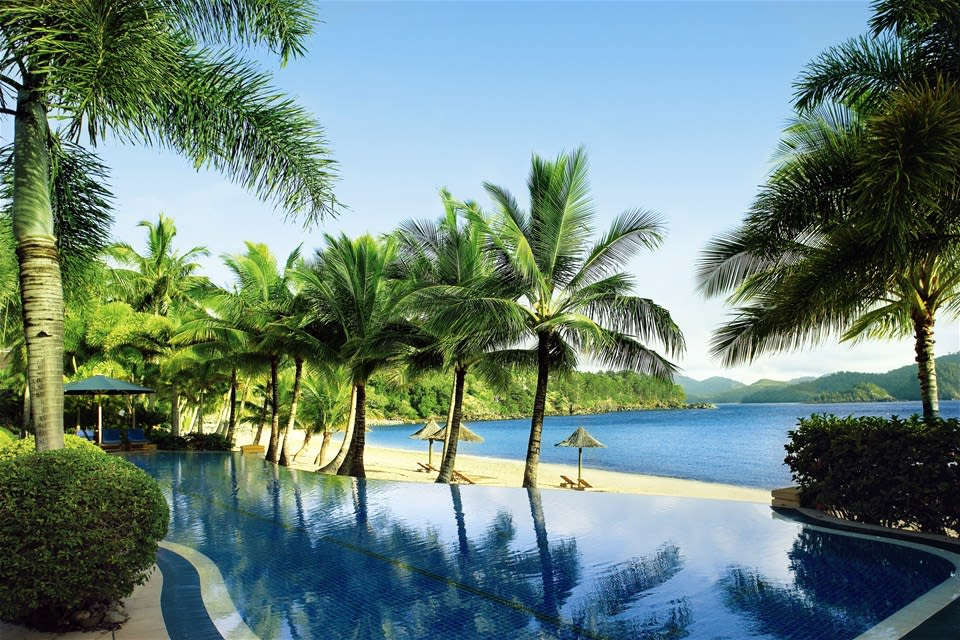 Palm tree lined pool overlooking a sandy beach and the Whitsunday Islands, Hamilton Island Resort, Queensland, Australia