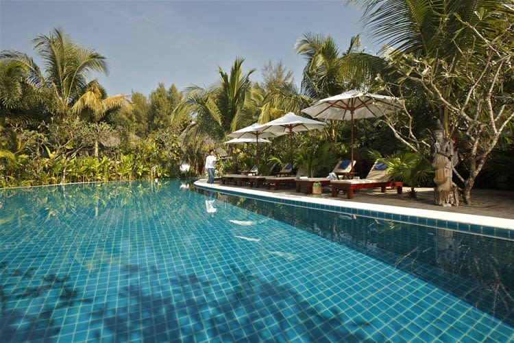 Blue tiled swimming pool surrounded by rainforest as a waiter walks past the loungers at Ngapali Bay Villas & Spa